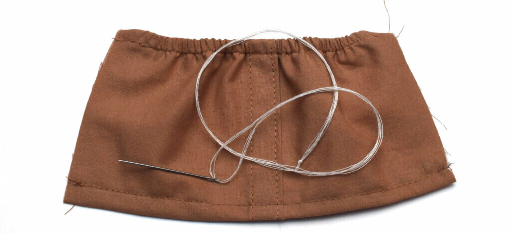 elastic skirt, sewing needle and thread